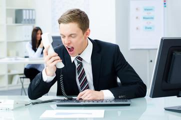 aufgebrachter geschäftsmann schreit ins telefon