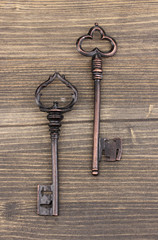 Two antique keys on wooden background