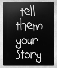 """""""Tell them your story"""" handwritten with white chalk on a blackbo"""