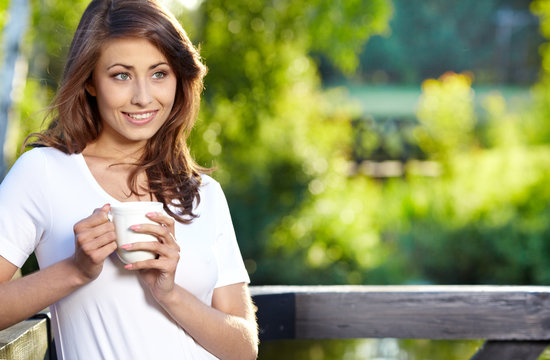 Young woman at  home terrace sipping tea from a cup