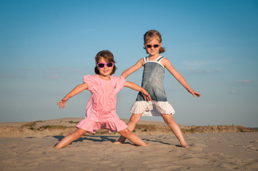 Two beautiful little girls playing on the sand