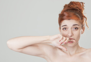 Red haired girl bites her finge