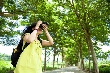 Young woman  in the green forest taking photo