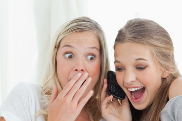 Shocked and happy sisters listening to a phone call