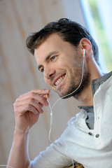 Young man talking on mobile phone with earphones