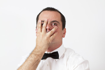 Guy with bow tie is holding hand on his face