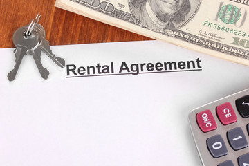 Rental agreement with dollars on wooden background close-up