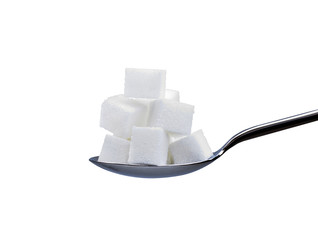 spoon full of refined white sugar cubes