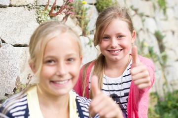 Zwei Mädchen vor Steinmauer Daumen up