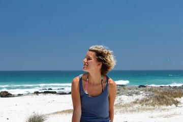 Frau am Strand mit Wind in den Haaren