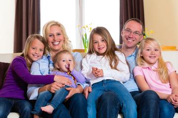 Familie auf der Couch daheim im Wohnzimmer