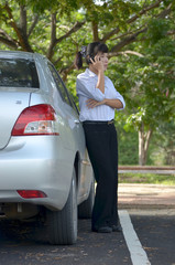 businesswoman speaking on mobile phone near her car