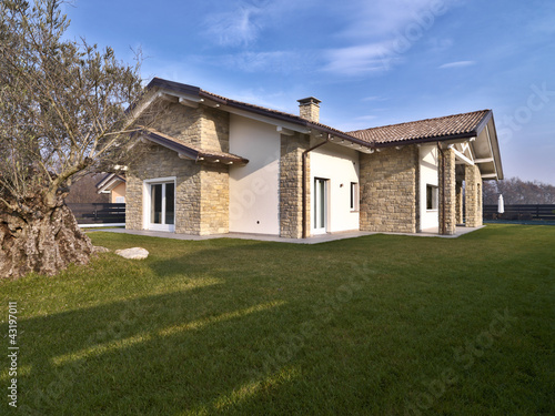 Villa moderna con giardino e muri di pietra immagini e for Casa moderna progetti