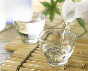 A cup of Japanese sake pouring from the sake decanter