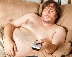 Overweight man watching tv and holding remote control