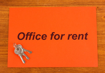 Advertise rental office on red paper on wooden background