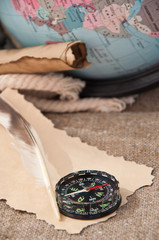 compass and old papers on the background of the globe