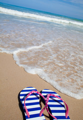 Colorful flip-flop sandals on sea beach