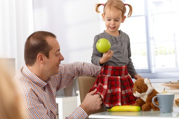 Father and daughter with green apple