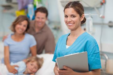 Nurse holding a clipboard next to a family