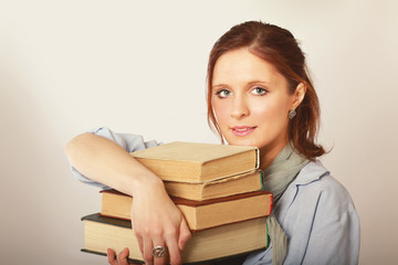 A college girl holding a pile of books, isolated on grey