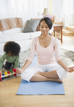 African American mother practicing yoga while son plays