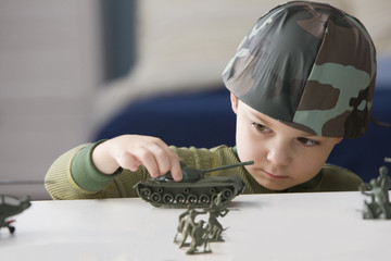 Caucasian boy playing with toy soldiers