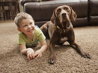 Caucasian boy sitting on floor with dog