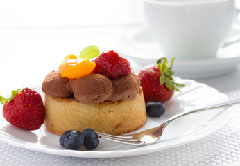 Fresh fruit tart with fork and coffee cup on background