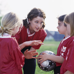 Coach talking to girl soccer players