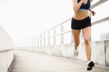 Hispanic woman running on urban walkway