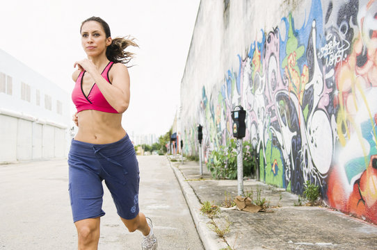 Hispanic woman running in urban area