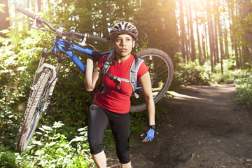 Hispanic woman carrying mountain bike in forest