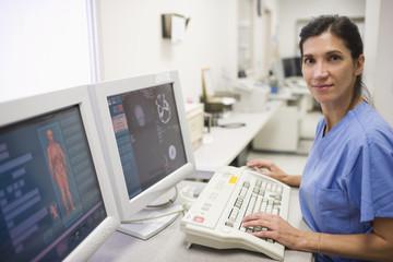 Hispanic nurse working on computer in hospital