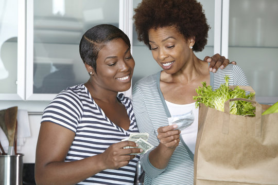 African American mother and daughter reviewing grocery bill