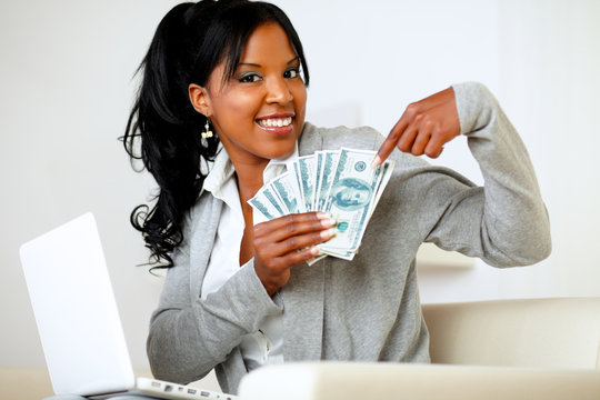 Happy woman pointing plenty of cash money