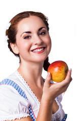 junge brünette Frau im Trachtenkleid mit Apfel