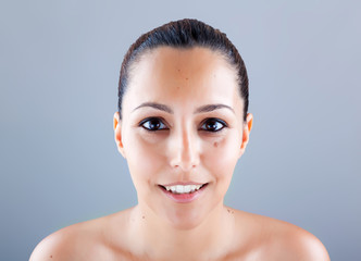 Closeup portrait of beautiful latin woman against grey backgroun