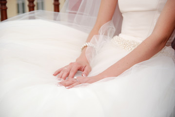Hands on a wedding white dress