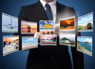 Businessman pushing many image in film button on the whiteboard.