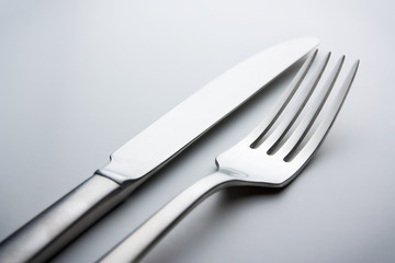 knife and fork on a neutral background