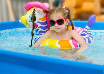 Funny little girl swims in a pool