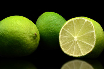 Three fresh limes isolated over black background