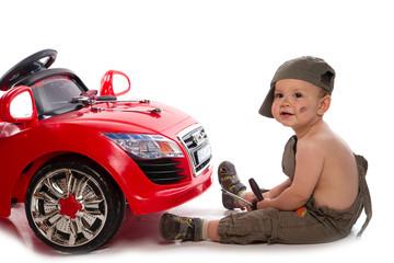 petit mécanicien devant sa voiture