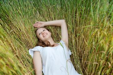 Beautiful woman smiles in wheat field