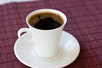 Wonderful white cup with hot black coffee on wooden background