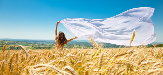 Young happy woman in wheat field with fabric