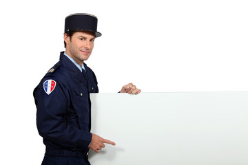 Man in a French gendarme uniform pointing at a blank board