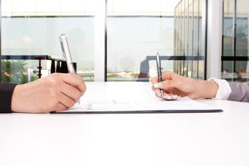 Hands of business people sitting at desk with documents sign up