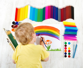 Child painting picture with brush in album using a lot of painti